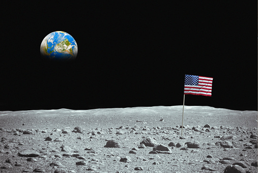 Flag of the USA on the moon with planet Earth on the sky. Photomontage, photo of the Earth has been used thanks to the NASA archive. https://www.nasa.gov/content/satellite-view-of-the-americas-on-earth-day