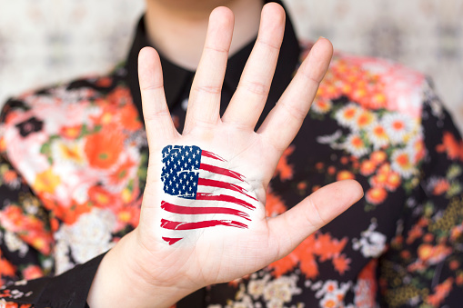 USA (United States of America) flag painted on open hand raised
