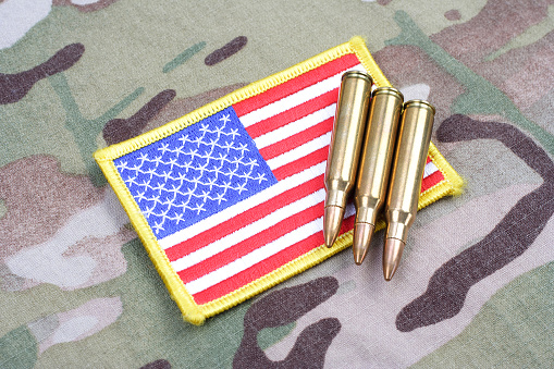 istock US ARMY flag patch and 5.56 mm rounds on camouflage uniform 1190926126