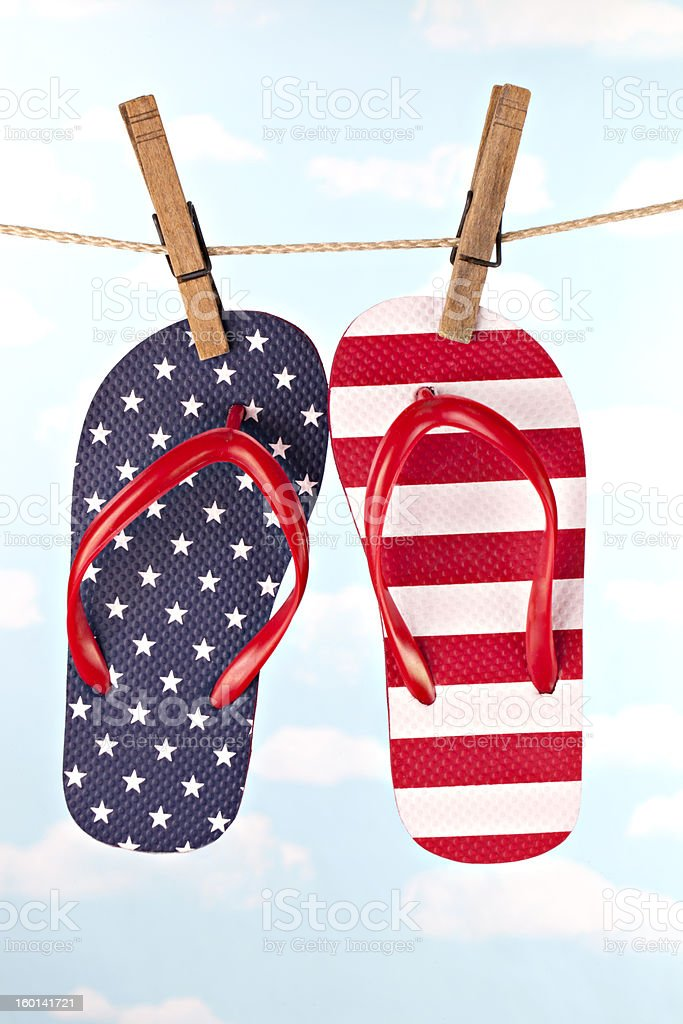 Flag patterned flip flop shoes hanging on clothes line royalty-free stock photo