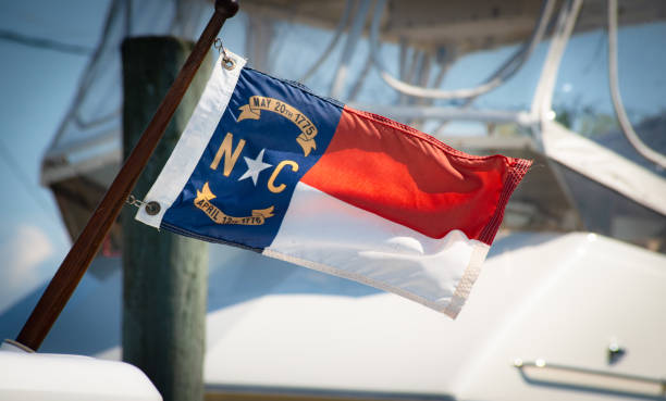 NC Flag A North Carolina flag waves in the wind, while a boat sits in the background. north carolina us state stock pictures, royalty-free photos & images