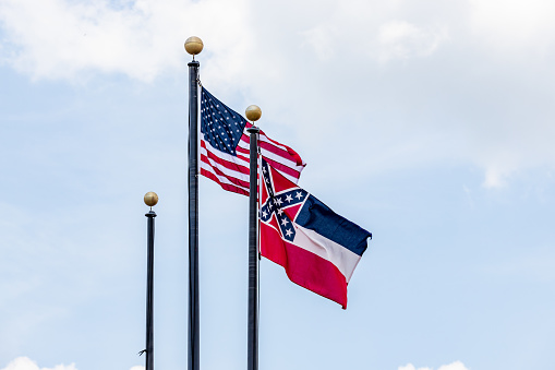 Flag poles with United States of America flag and State of Mississippi Flag waving in the wind against blue sky.