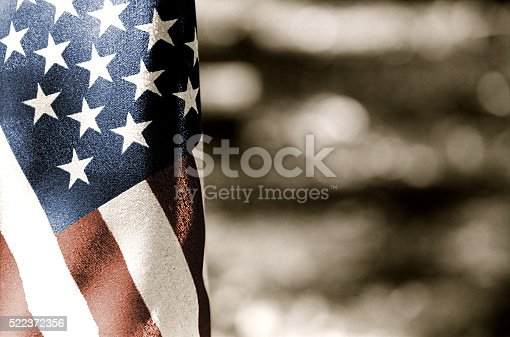 A black and white picture of US Flag selectively toned  red, white and blue
