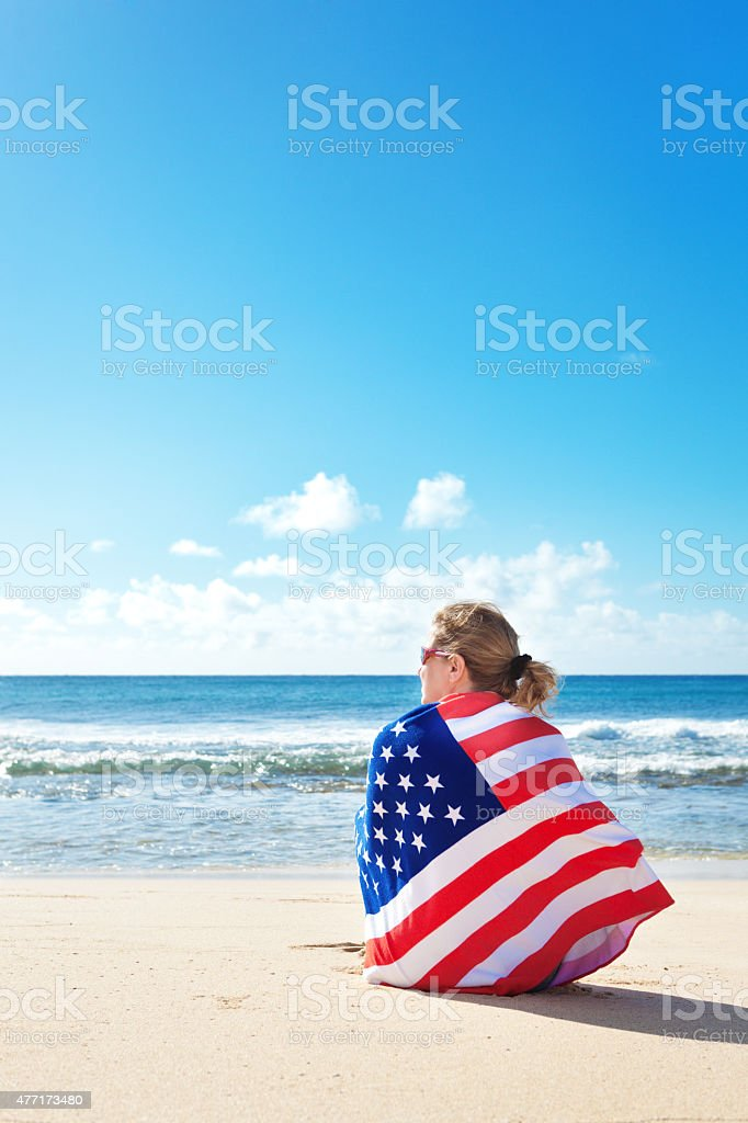 USA Flag Towel Wrapped Woman Vacationing on Tropical Hawaiian Beach stock photo