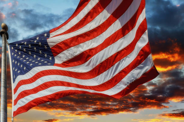 Flag USA over beautiful Sunset sunrise with clouds, in pink and purple shades stock photo