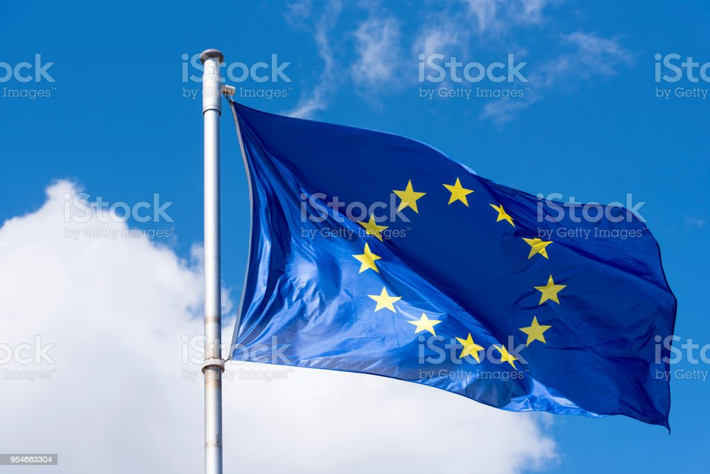 Bandera de la UE que agita contra el cielo azul - foto de stock