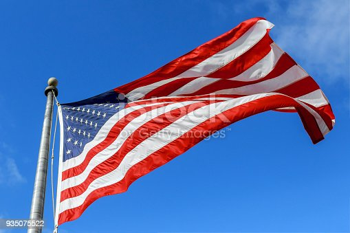 istock USA flag waving against clear blue sky on bright sunny day 935075522