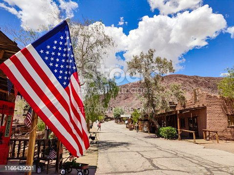 Calico Ghost Town California, USA. May 29, 2019. US flag waving, Calico theme park background, blue sky, sunny spring day