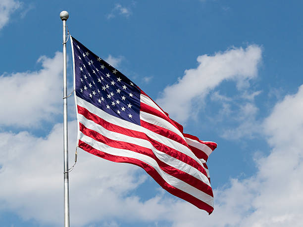 us flag waving in blue cloudy sky - national anthem stock photos and pictures