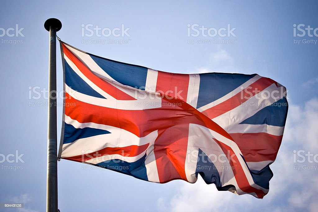 UK flag waving in sunny blue skies stock photo