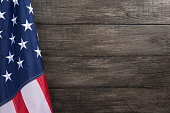 US flag with embossed stars, hanged against old wooden wall background