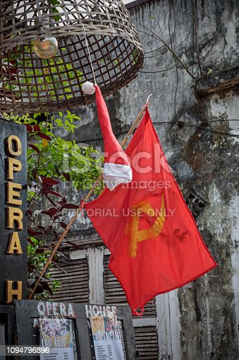 Luang Prabang, Laos - December 9, 2018: Red flag with hammer and sickle and a christmas hat outside a house in Luang Prabang, the former capital of Laos