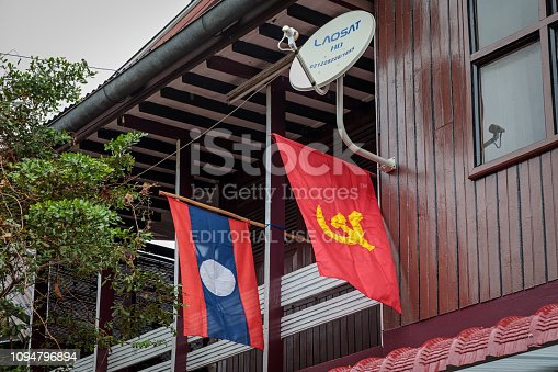 Luang Prabang, Laos - December 8, 2018: Red flag with hammer and sickle outside a house in Luang Prabang, the former capital of Laos