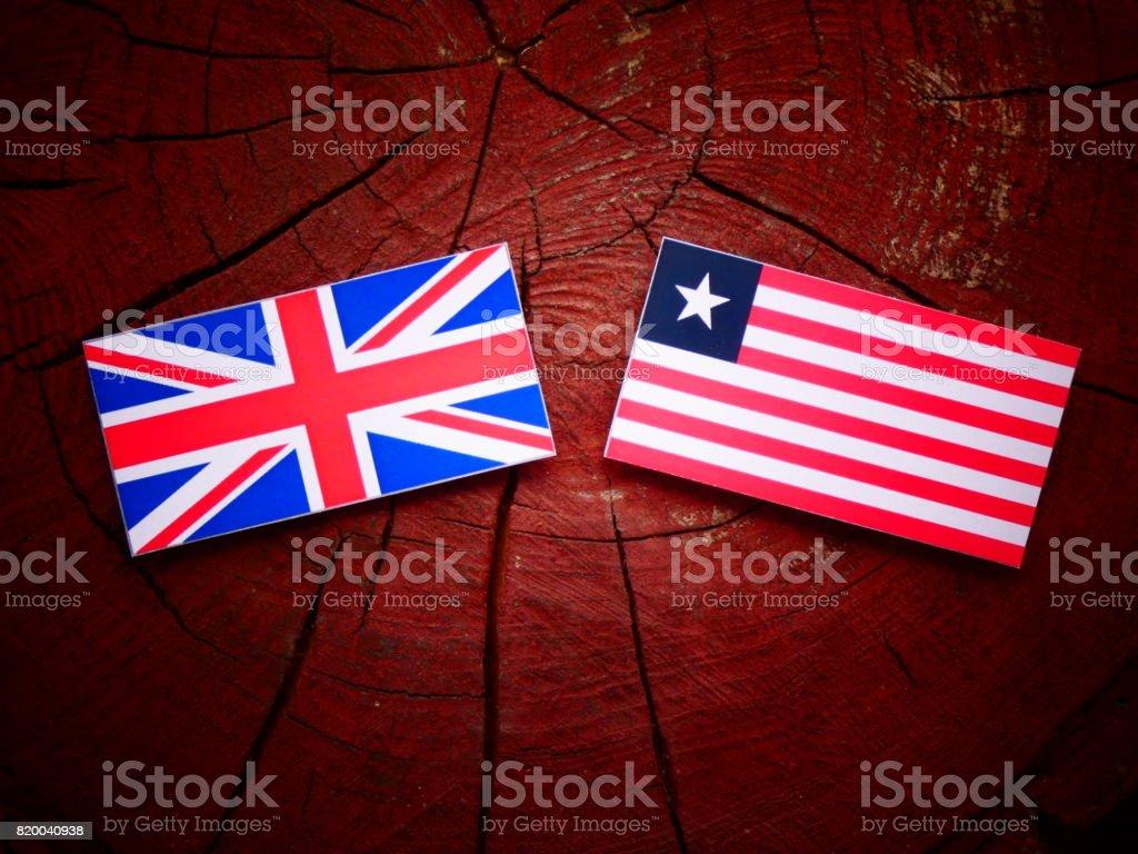 UK flag with Liberian flag on a tree stump isolated stock photo