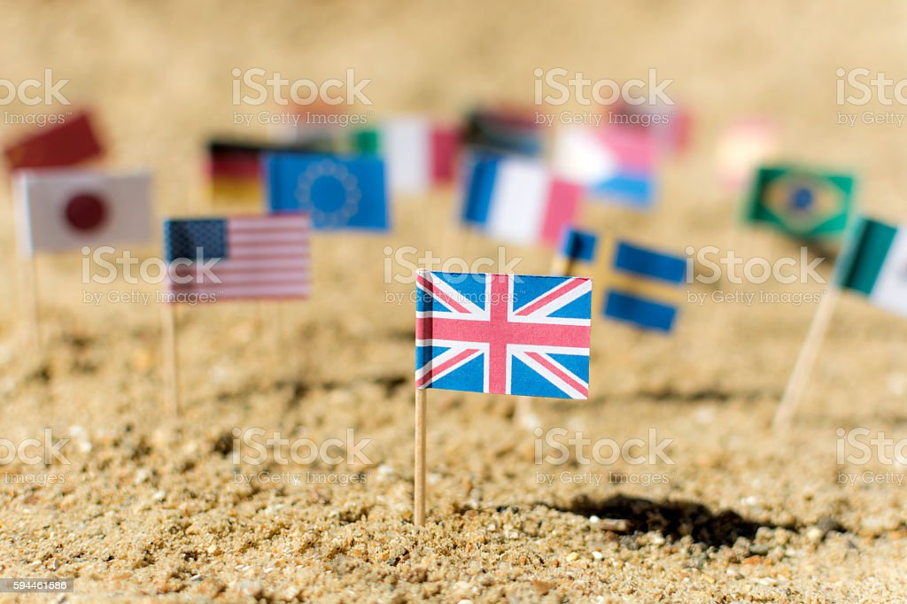 UK Flag with other world flags on beach stock photo