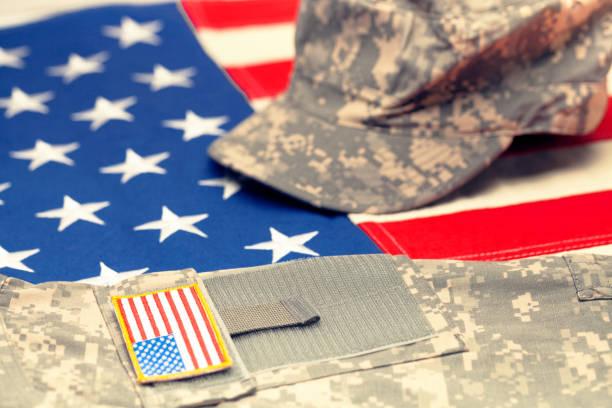 usa-flagge mit us militärische uniform drüber - studio gedreht. gefilterten bild: gecrosst wird vintage-effekt. - militäruniform stock-fotos und bilder