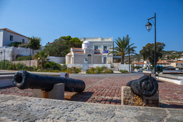 Flags and ancient cannon at Spetses island Greece Flag of Greece stock photo