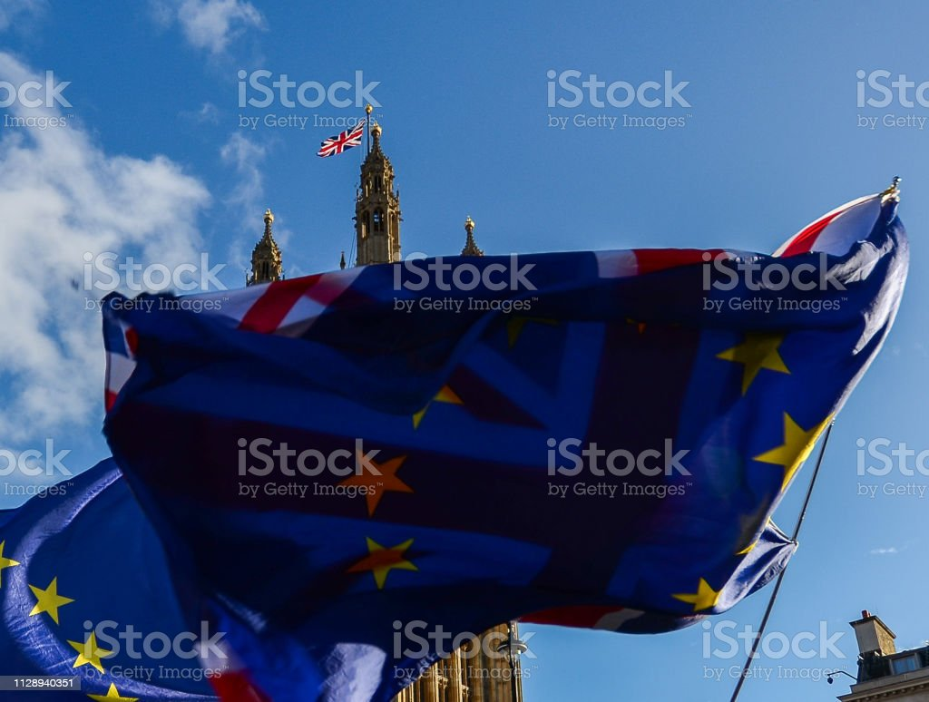 EU flags and British flag in front of each other with Victoria Tower, Westminster, London, UK in background - Brexit theme stock photo
