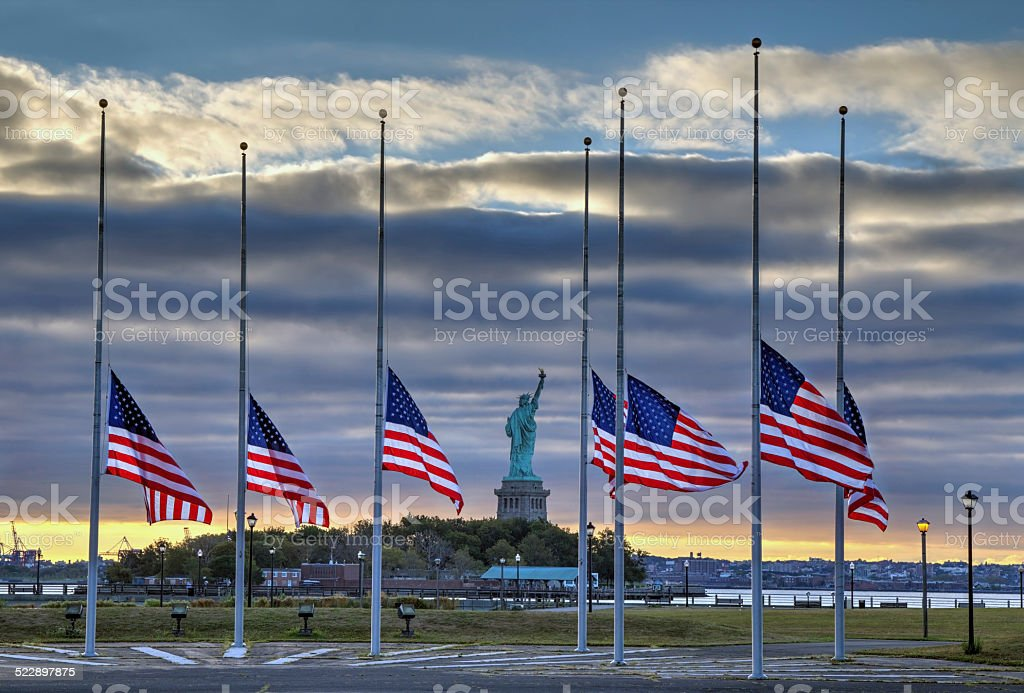 US flags at half staff and Statue of Liberty stock photo