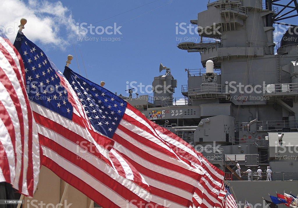 US Flags Beside Battleship Missouri Memorial with Four Sailors stock photo