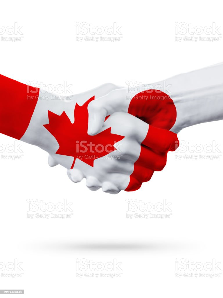Flags Canada, Japan countries, partnership friendship handshake concept. royalty-free stock photo