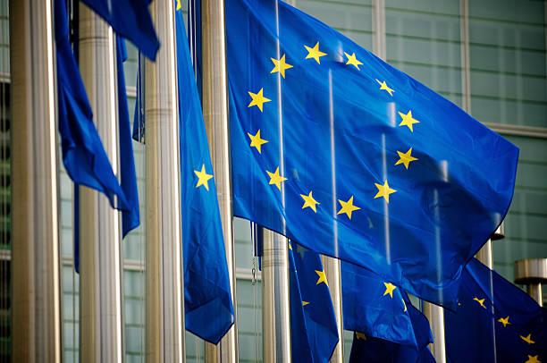 Banderas ondeando de la UE en la Comisión Europea el edificio de Bruselas Bélgica - foto de stock