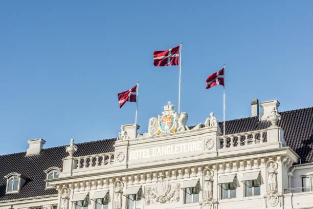 fahnen im wind auf die fassade des hotel d´angleterre in kopenhagen - hotels in kopenhagen stock-fotos und bilder