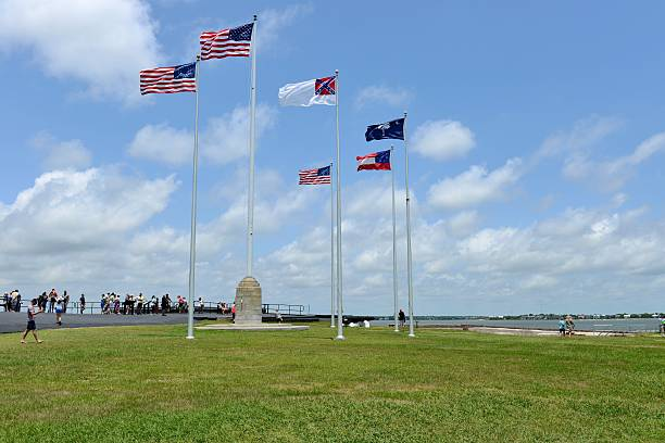 Flags flying over Fort Sumter Charleston, South Carolina, USA - June 7, 2015: Six flags, the 50-star United States flag and five historic flags, flying on the top of Fort Sumter -- the starting place of the America Civil War. These five historic flags, from left to right, are: The 35-star United States Flag (1865); The 33-star United States Flag -- also called Fort Sumter Flag (1861); The Second National Flag of the Confederacy, or Stainless Banner (1863); The First National Flag of the Confederacy, or Stars and Bars (1861); The South Carolina State Flag (since 1861). They represent the flags that flew over Fort Sumter during the Civil War. civil war memorial minnesota stock pictures, royalty-free photos & images