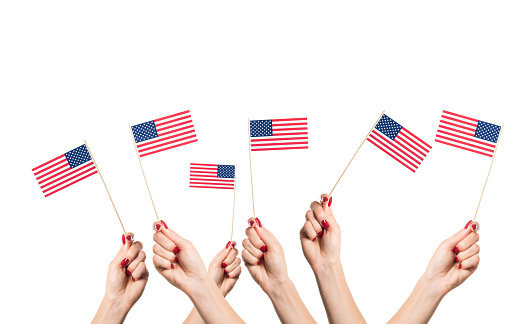 Usa paper national flags in woman hands against white background. 4th july independence day concept