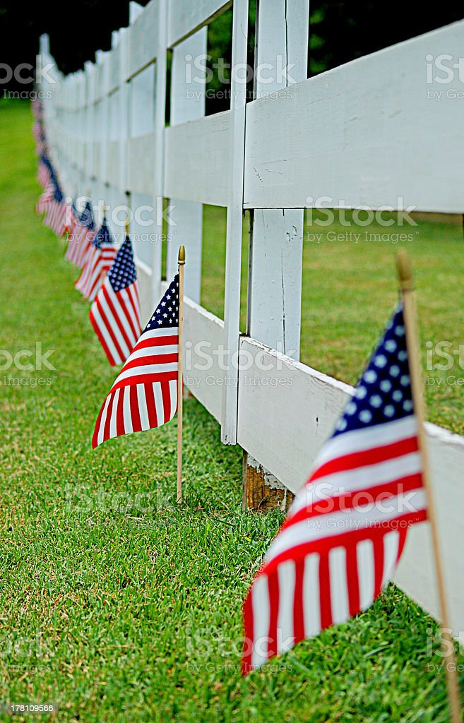 Flags line a residential fence on the July Fourth Holiday royalty-free stock photo