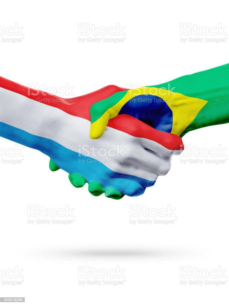 Flags Luxembourg, Brazil countries, partnership friendship handshake concept. photo libre de droits