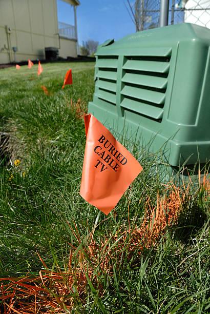 flags mark buried cable in residential yard - gömülü stok fotoğraflar ve resimler