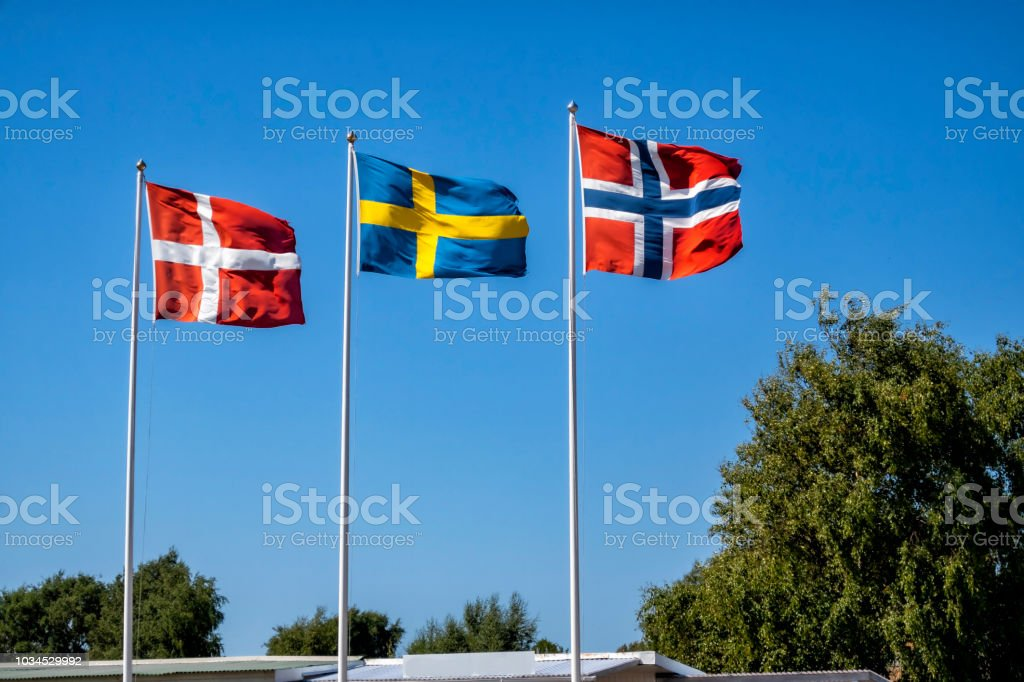 Sweden, Norway and Denmarks flags against vibrant blue sky