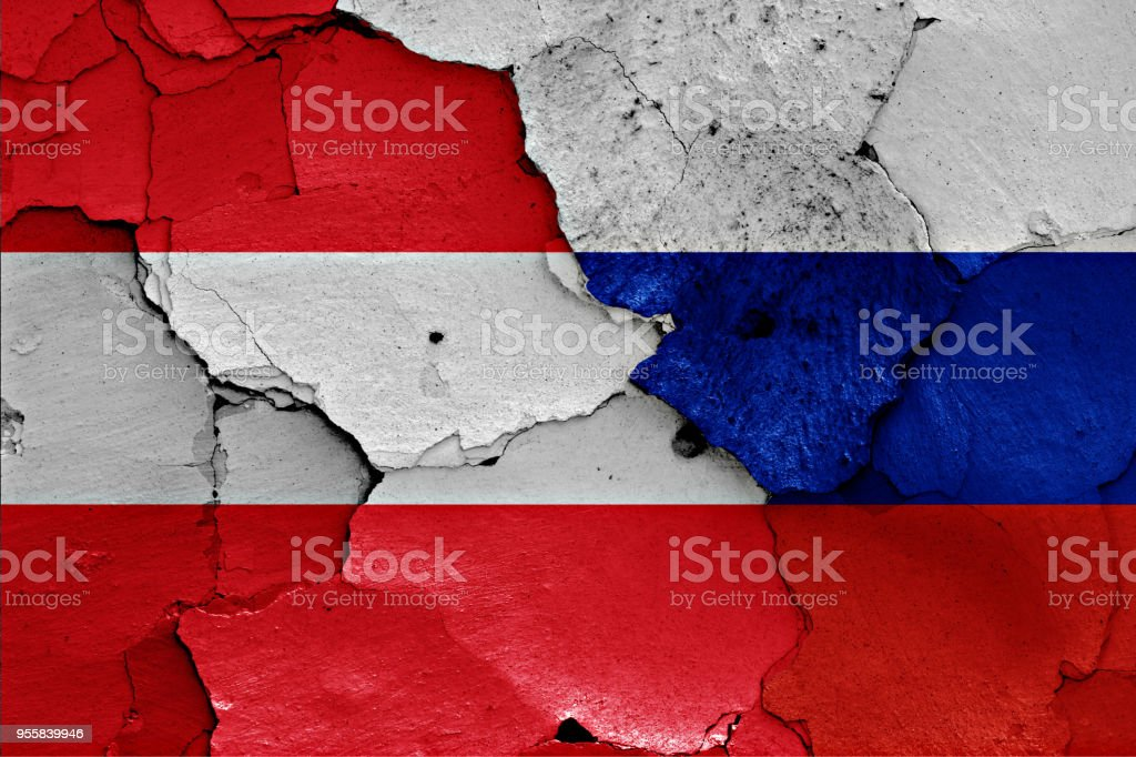 flags of Austria and Russia painted on cracked wall stock photo
