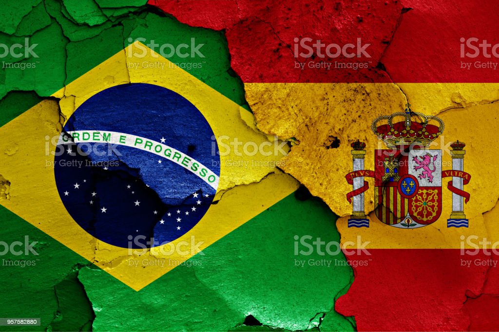 flags of Brazil and Spain painted on cracked wall stock photo