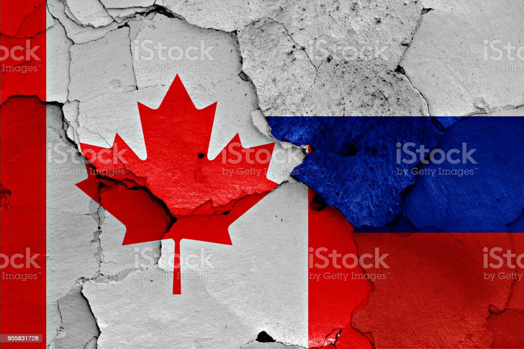 flags of Canada and Russia painted on cracked wall stock photo
