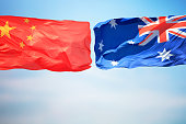 Chinese and Australian flags amid blue skies