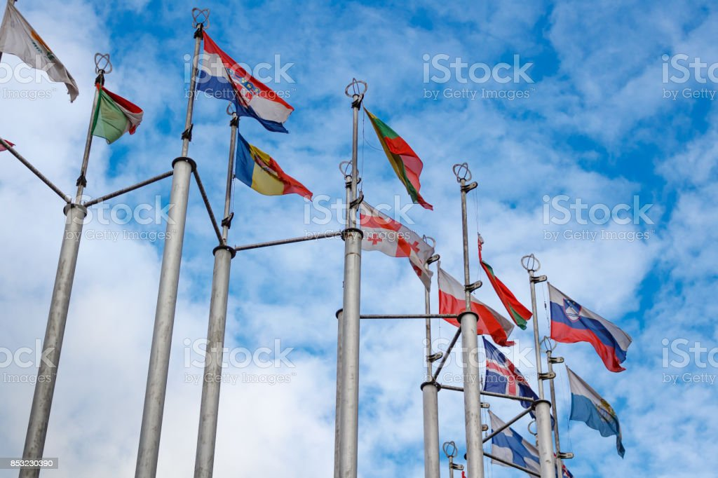 Flags of different countries on blue sky background stock photo