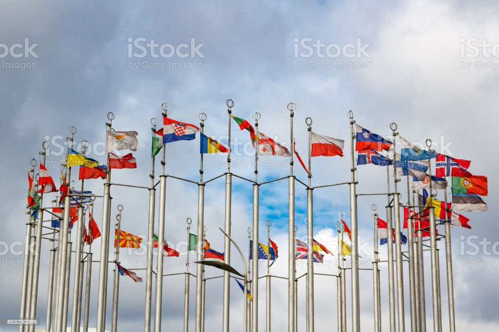 Flags of different countries on cloudy sky background stock photo