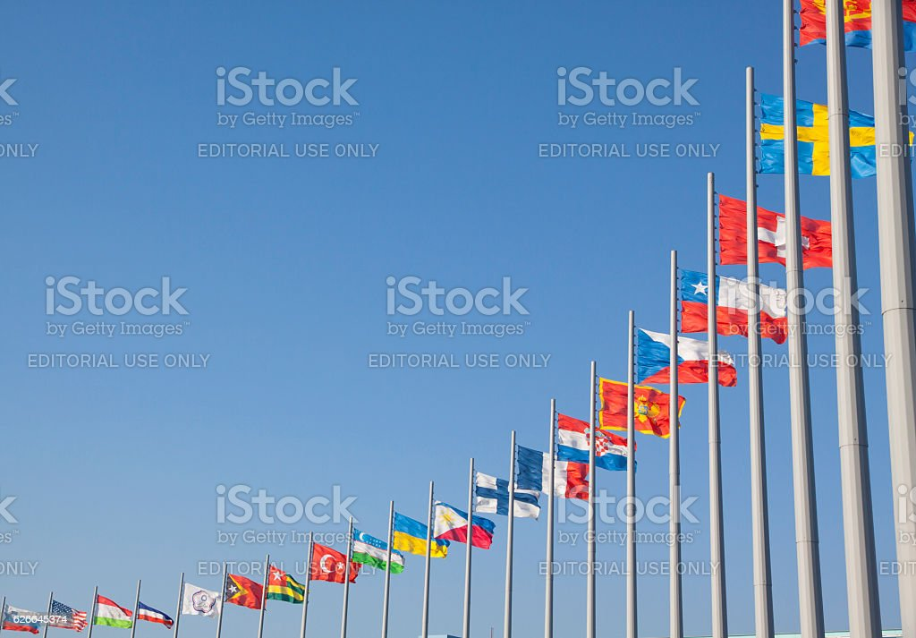 Flags of different countries on the flagpole stock photo