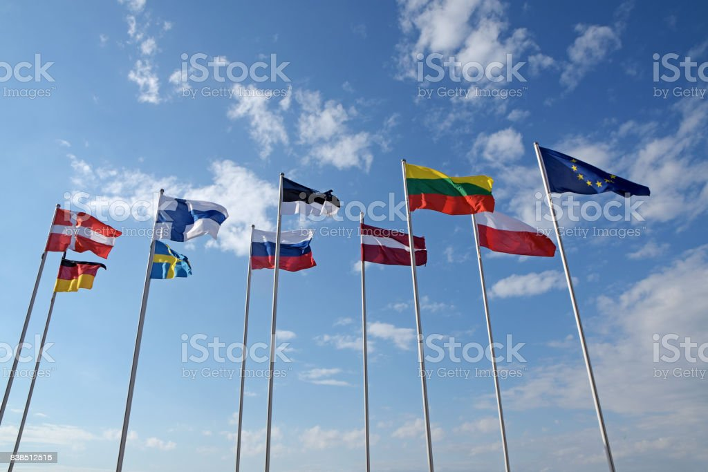 Flags of different countries, the national symbols or signs of Denmark, Germany, Finland, Sweden, Estonia, Russia, Austria, Lithuania, Poland and Europe, fluttering at high poles in the wind against the blue sky with clouds on a sunny day stock photo