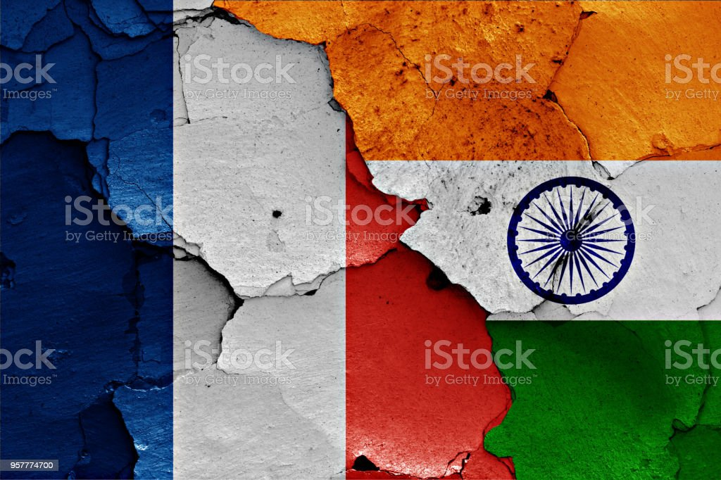 flags of France and India painted on cracked wall stock photo