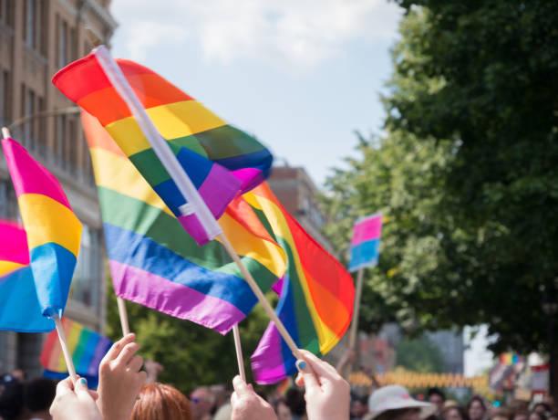 Sinalizadores de flutuador de orgulho gay no ar durante desfile em Montreal, Canadá - foto de acervo