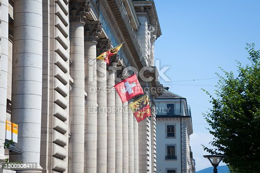 Picture of Geneva and Swiss flags during a sunny afternoon waiving in the sky in fornt of Hotel des Postes, the main post office of Swiss post in Geneva, switzerland.