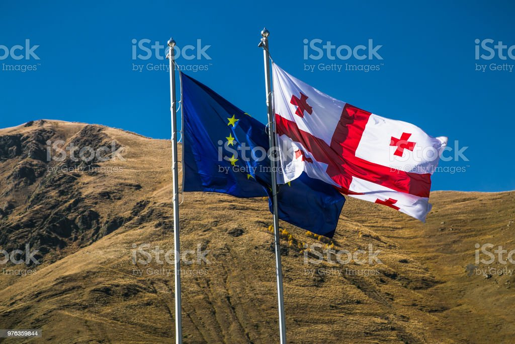 Flags of Georgia and European Union hanging on poles, waving in the wind. Georgia stock photo