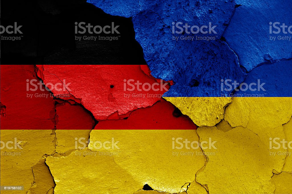 flags of Germany and Ukraine painted on cracked wall stock photo