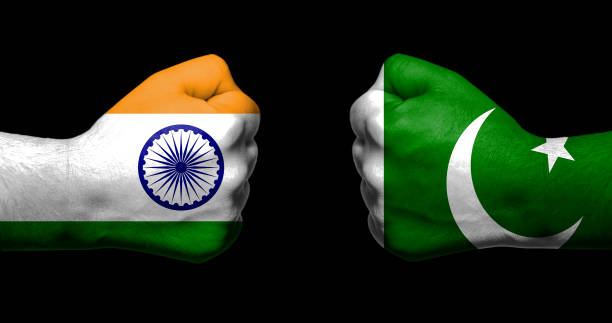 flags of india and pakistan painted on two clenched fists facing each other on black background/india - pakistan relations concept - pakistano foto e immagini stock