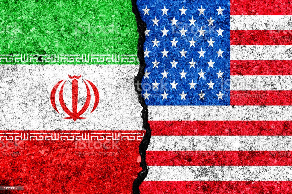 Flags of Iran and USA painted on cracked wall background/Iran versus USA conflict concept stock photo