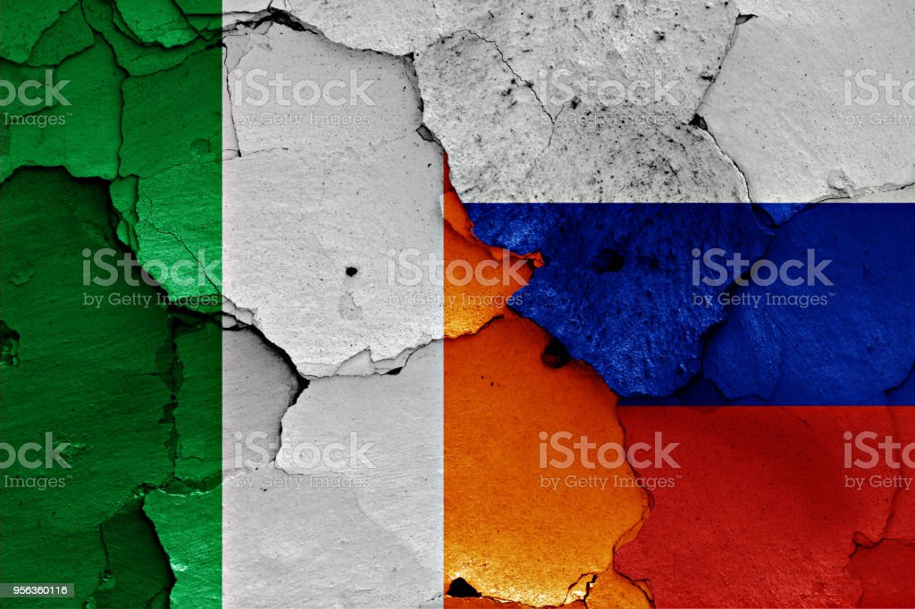 flags of Ireland and Russia painted on cracked wall stock photo