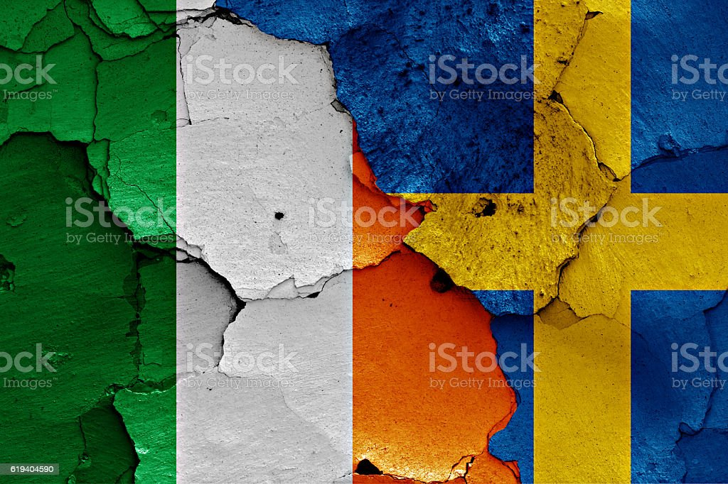 flags of Ireland and Sweden painted on cracked wall stock photo